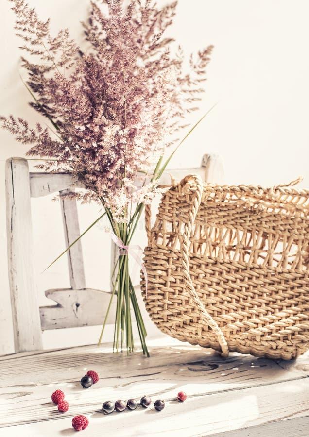 Uitstekend de zomerstilleven Een gelopen zak en droge oren van gras op een oude witte stoel eenvoudige uitstekende punten stock afbeelding