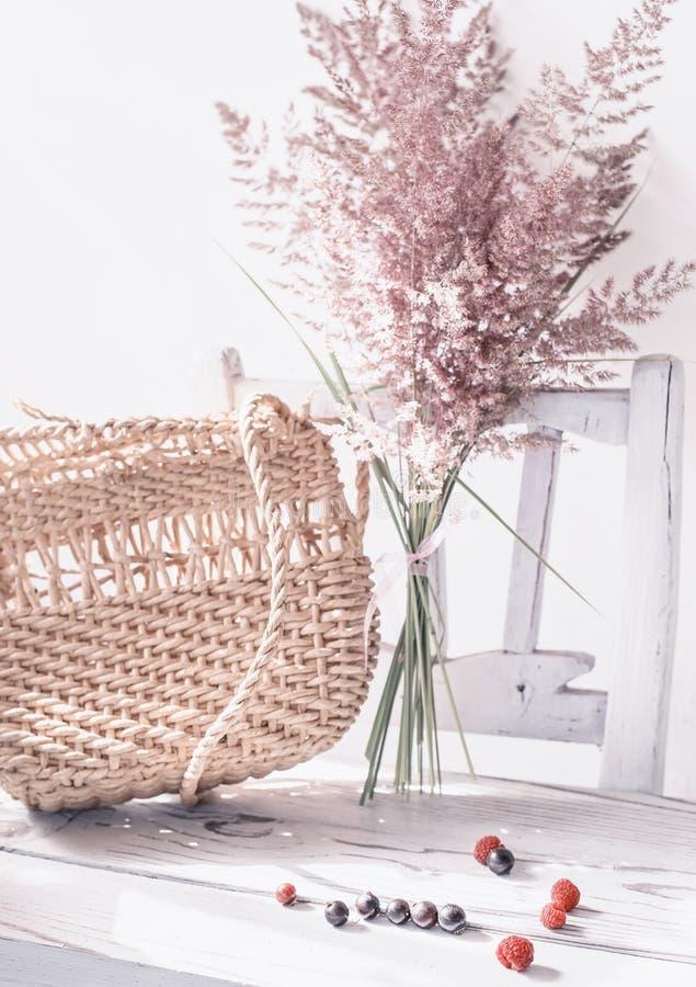 Uitstekend de zomerstilleven Een gelopen zak en droge oren van gras op een oude witte stoel stock foto's