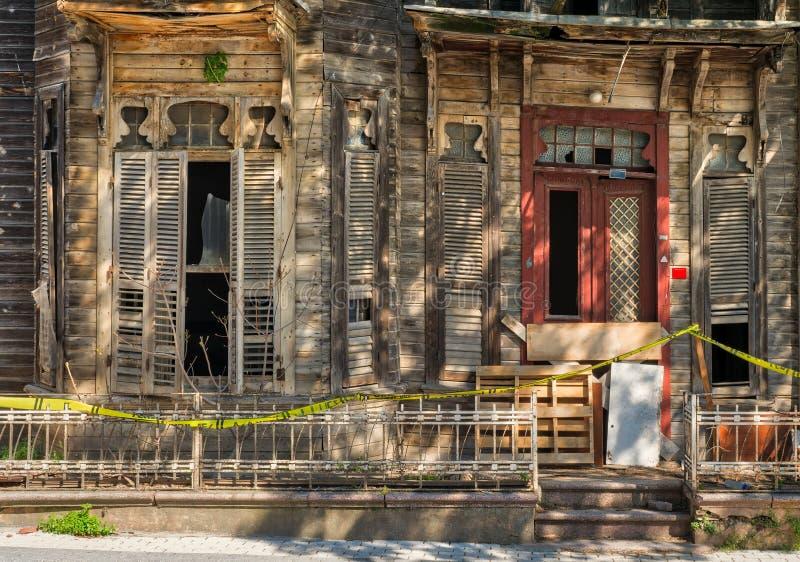 Uitstekend deur en venster op verlaten blokhuis met klein balkon en geroeste metaalomheining stock foto's