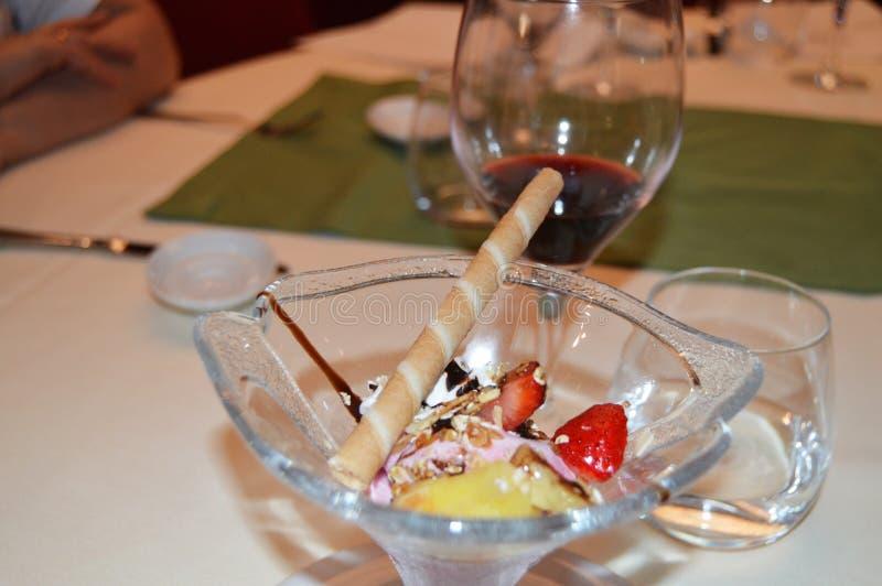 Uitstekend die dessert met roomijs, met aardbeien, fruit en wijn, diner in het restaurant wordt verfraaid stock afbeelding
