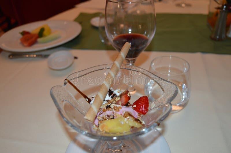 Uitstekend die dessert met roomijs, met aardbeien, fruit en wijn, diner in het restaurant wordt verfraaid stock fotografie
