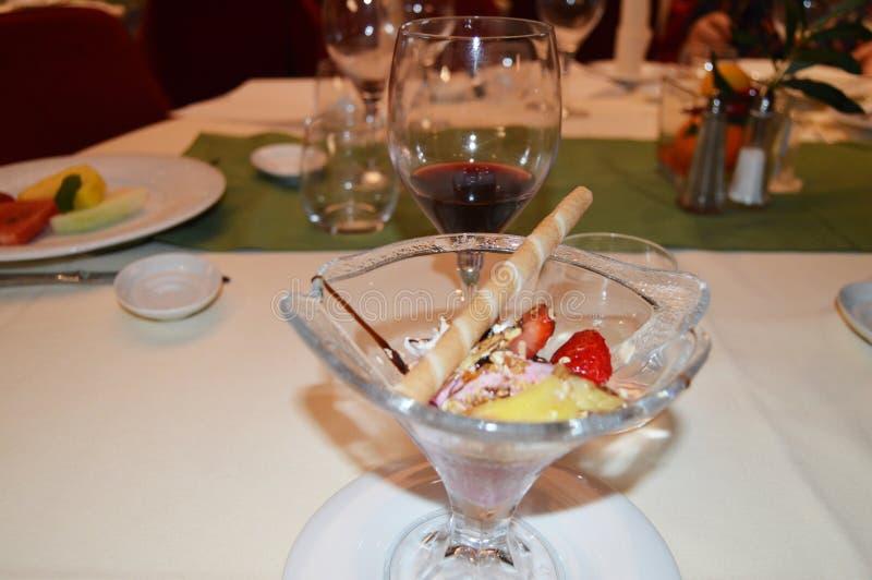 Uitstekend die dessert met roomijs, met aardbeien, fruit en wijn, diner in het restaurant wordt verfraaid royalty-vrije stock afbeelding
