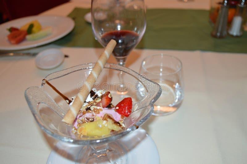 Uitstekend die dessert met roomijs, met aardbeien, fruit en wijn, diner in het restaurant wordt verfraaid royalty-vrije stock foto's
