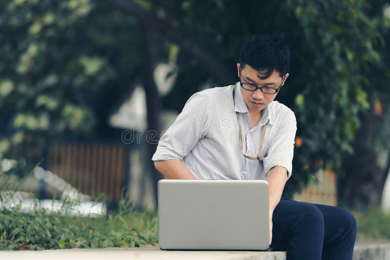 Uitstekend gestemd beeld van de ontspannen jonge Aziatische bedrijfsmens die met laptop bij openbaar park werken stock afbeeldingen