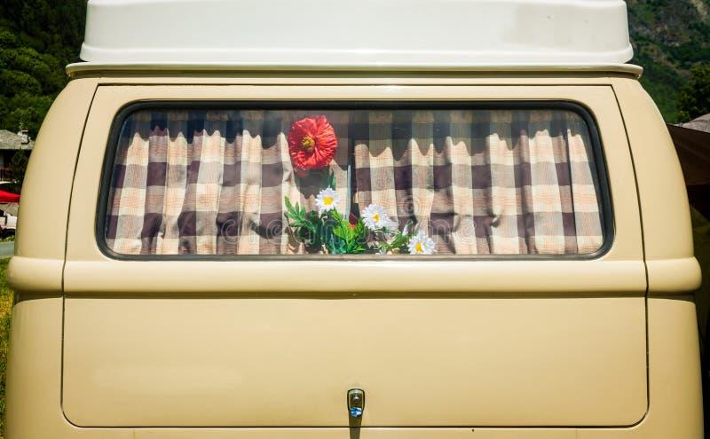 Uitstekend gordijn op het venster van een oude bestelwagen met bloem stock foto