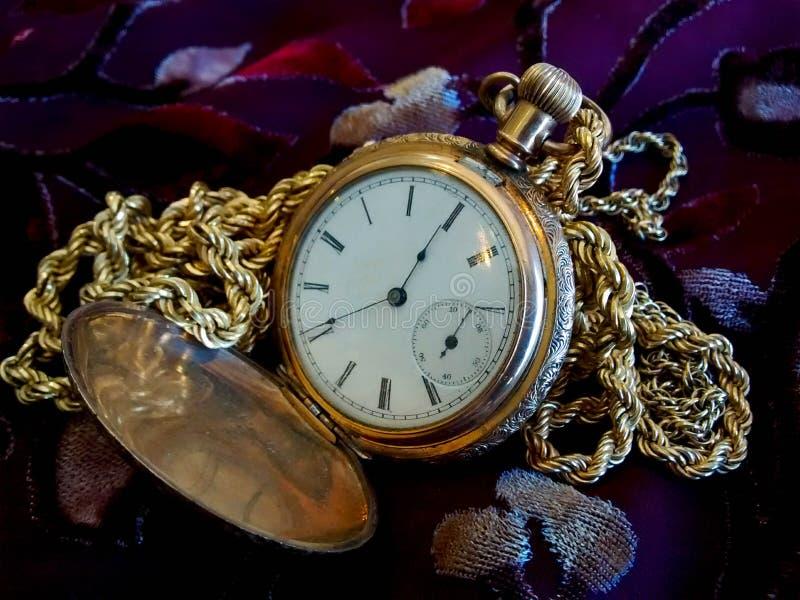 Uitstekend gouden zakhorloge met ketting op stoffenachtergrond royalty-vrije stock afbeeldingen