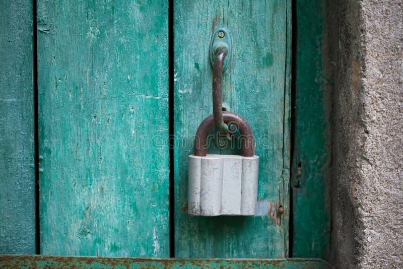 Uitstekend hangend slot, gesloten groene houten deur Groene en gele bladeren op een boomboomstam stock foto's