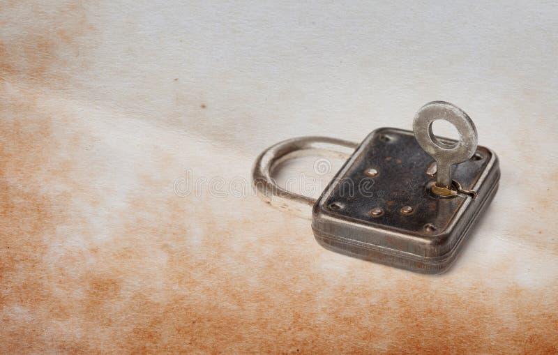 Uitstekend hangslot met sleutel in gat, oude geweven document achtergrond De ruimte van het exemplaar stock afbeeldingen