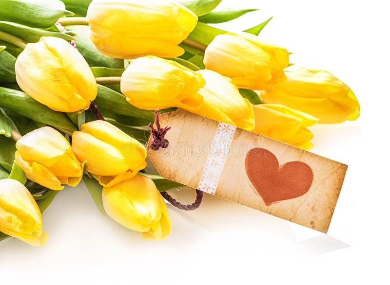 Uitstekend hartetiket op een bos van gele tulpen stock afbeelding
