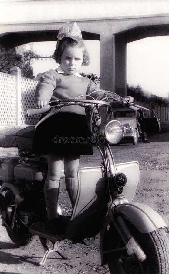 Uitstekend meisje op oude autoped royalty-vrije stock afbeelding