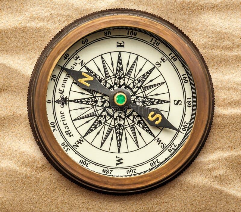 Uitstekend messingskompas op zand stock foto's