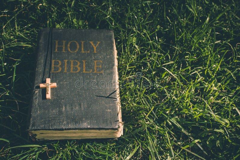 Uitstekend oud heilig bijbelboek, grunge geweven dekking met houten christelijk kruis Retro gestileerd beeld op grasachtergrond royalty-vrije stock foto