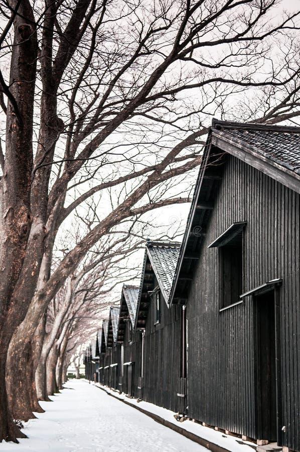 Uitstekend oud Japans zwart pakhuis in de wintersneeuw en boom lin royalty-vrije stock afbeeldingen