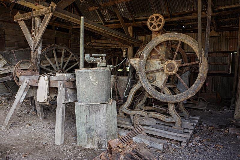 Uitstekend oud landbouwbedrijfmateriaal in loods stock afbeeldingen