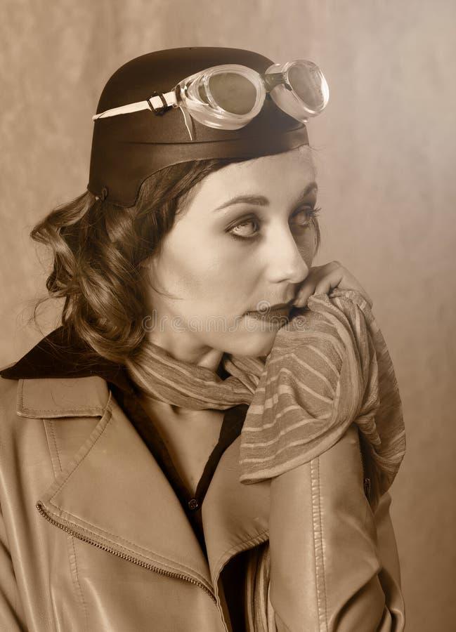 Uitstekend stijlportret van vliegeniersvrouw die beschermende brillen, leerjasje en sjaal dragen royalty-vrije stock foto's