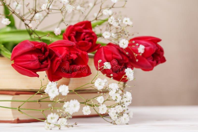 Uitstekend stilleven met de lente rode tulpen en boeken op een beige achtergrond Moederdag, de dagconcept van Vrouwen royalty-vrije stock foto