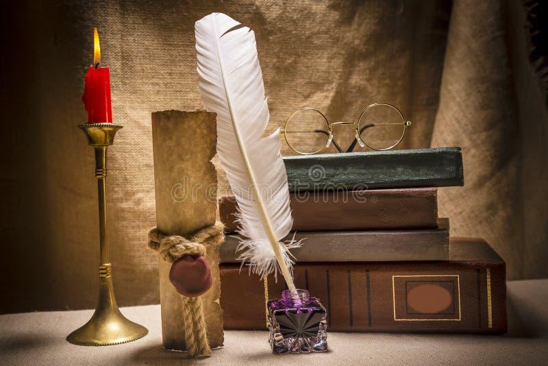 Uitstekend stilleven met glazen op oude boeken dichtbij inkstand, veer, oud document en brandende kaars op canvasachtergrond royalty-vrije stock foto