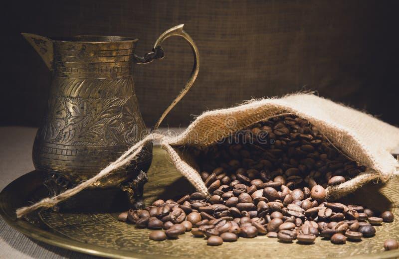 Uitstekend stilleven met hoop van koffiebonen in jutezak dichtbij de oude pot van de koper Turkse koffie op bronsdienblad tegen c royalty-vrije stock foto's