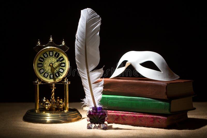 Uitstekend stilleven met theatermasker op oude boeken dichtbij inkstand, veer, oude klok tegen zwarte achtergrond onder lichtstra royalty-vrije stock afbeeldingen