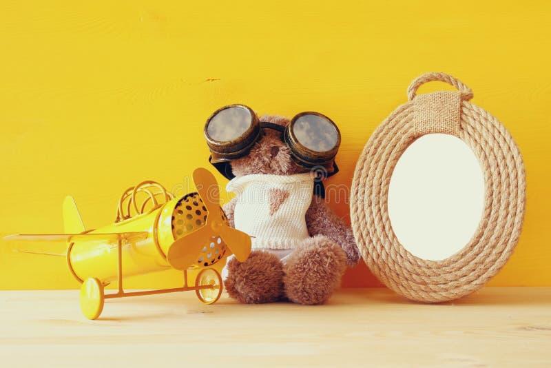 uitstekend stuk speelgoed vliegtuig en leuke teddybeer naast leeg kader stock foto's