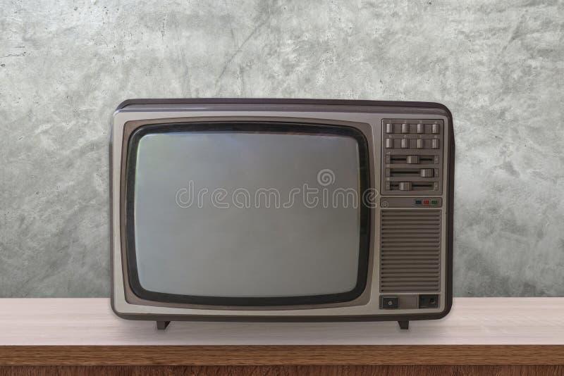 Uitstekend TV-vakje op houten lijst en cementmuurachtergrond stock afbeeldingen