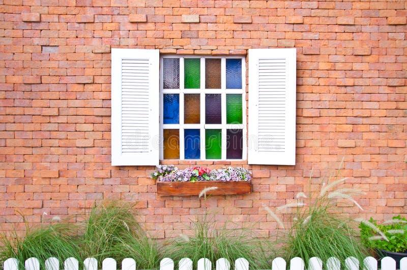 Uitstekend venster met blinden die en verse bloemen met gekleurde glas en bakstenen muur openen stock afbeeldingen