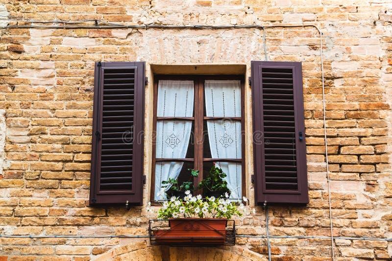 Uitstekend venster met bloemen en blinden in Italië royalty-vrije stock foto