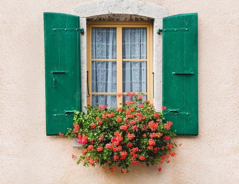 Uitstekend venster met bloemen en blinden in Zwitserland stock afbeelding