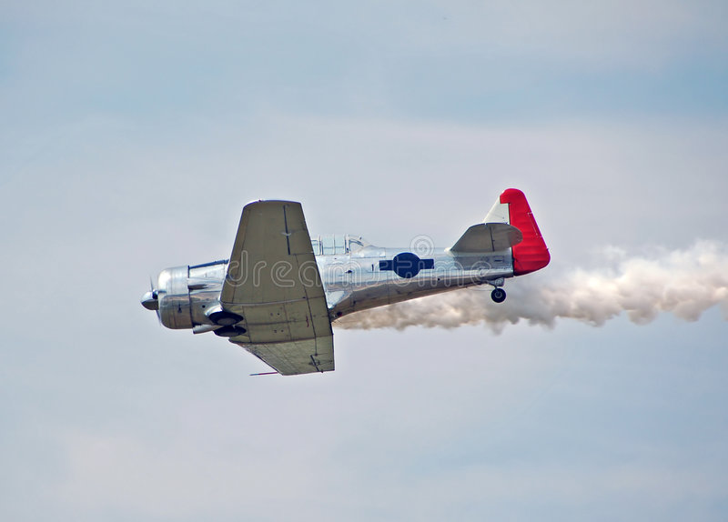 Uitstekend vliegtuig t-6 duikt en rookt stock afbeelding