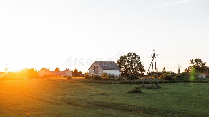 Uitstekend wit huis op het gebied in het dorp op de achtergrond de achtergrond van een heldere oranje zonsondergang Rust in het p stock foto's