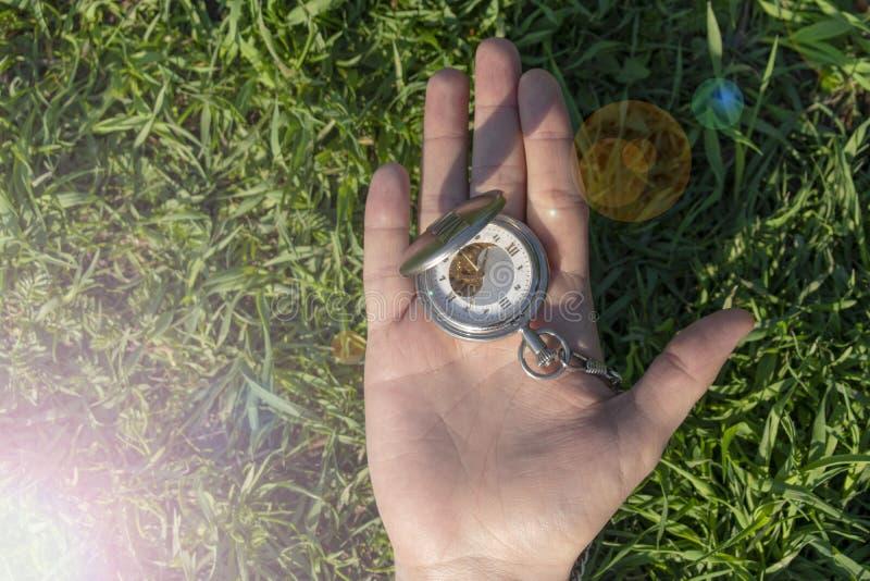 Uitstekend zakhorloge in mannelijke hand op een achtergrond van groen gras Steampunkhorloge Het klokmechanisme is gedeeltelijk zi royalty-vrije stock afbeelding