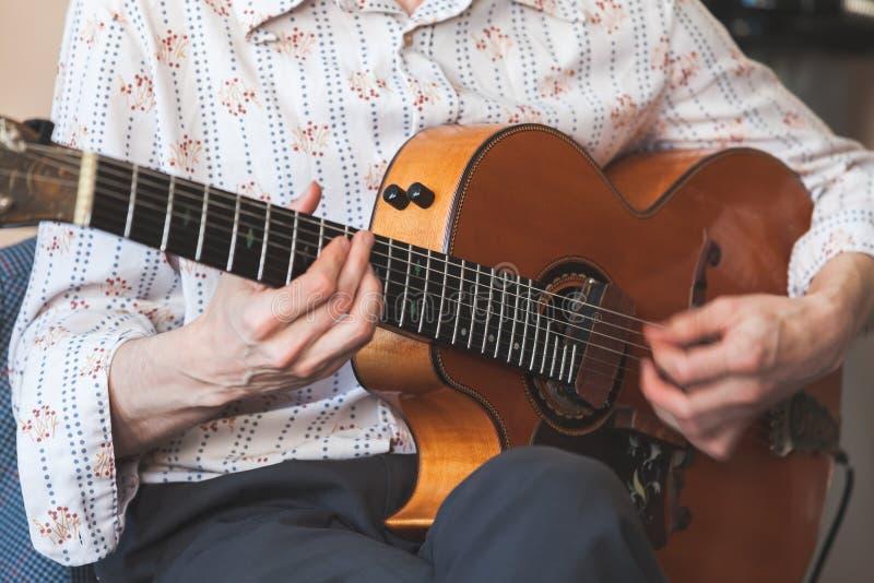 Uitstekende akoestische gitaar in handen stock afbeelding