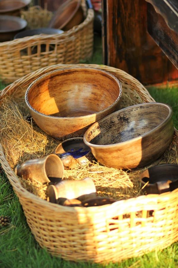 Uitstekende authentieke houten platen en mokken in zonovergoten mand met hey stock foto