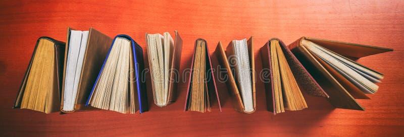 Uitstekende boeken die zich op houten achtergrond bevinden - hoogste mening stock foto's