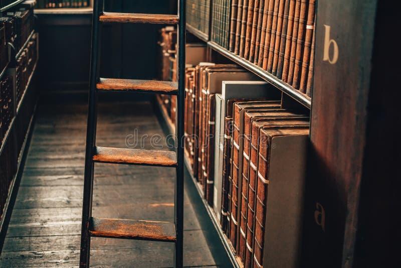 Uitstekende boeken in leerdekking op boekenrekkabinet met ladder op houten vloer royalty-vrije stock afbeeldingen