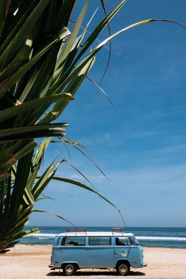 Uitstekende brandingsauto die op de tropische strandkust wordt geparkeerd Vrije tijdsreis in de zomer De ruimte van het exemplaar royalty-vrije stock afbeelding