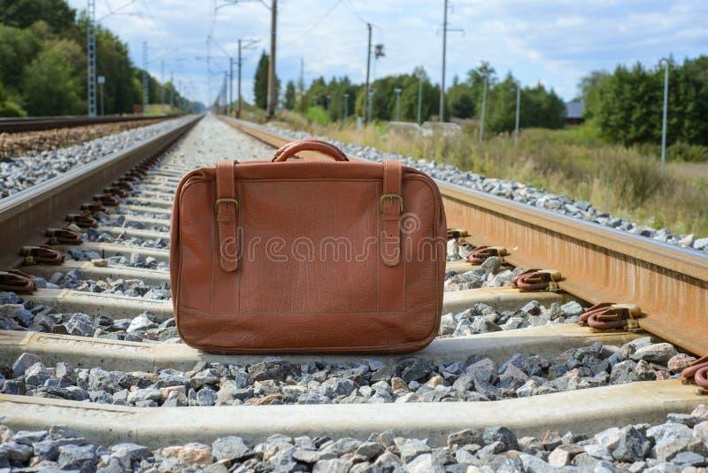 Uitstekende bruine koffer op de spoorweg stock foto