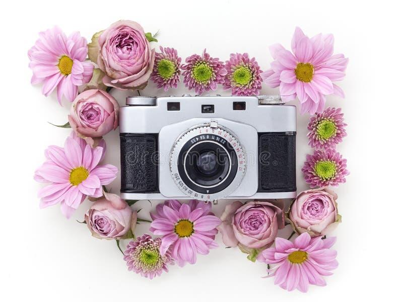 Uitstekende camera en roze bloem op witte achtergrond Vlak leg, hoogste mening stock afbeeldingen