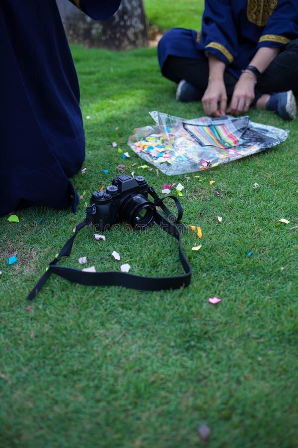 Uitstekende camera op gras met beetjes van gekleurd document stock afbeeldingen