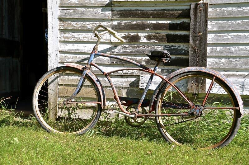Uitstekende die fiets naast een doorstane oude loods wordt geparkeerd stock foto's