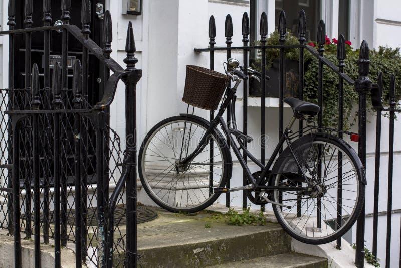 Uitstekende fiets met mand op de portiek Ingangsdeur aan woningbouw in Londen Typische deur in de Engelse stijl royalty-vrije stock afbeelding