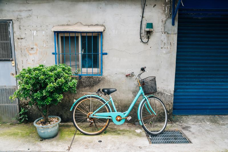 Uitstekende fiets tegen oude huismuur in Taipeh, Taiwan stock foto