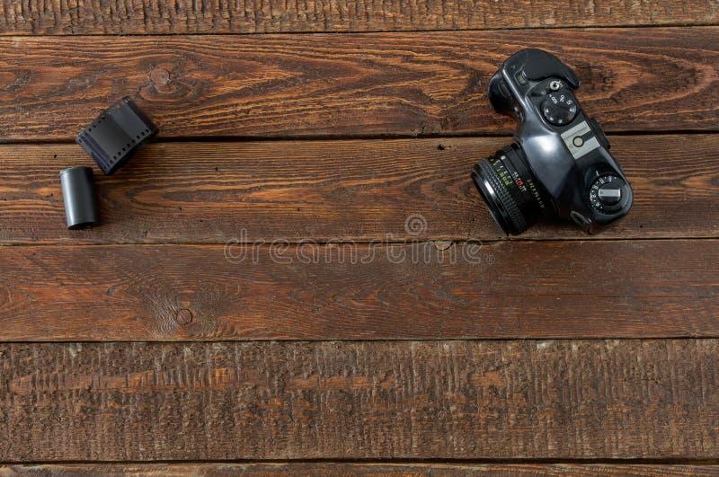 Uitstekende filmcamera en film op houten lijst stock foto