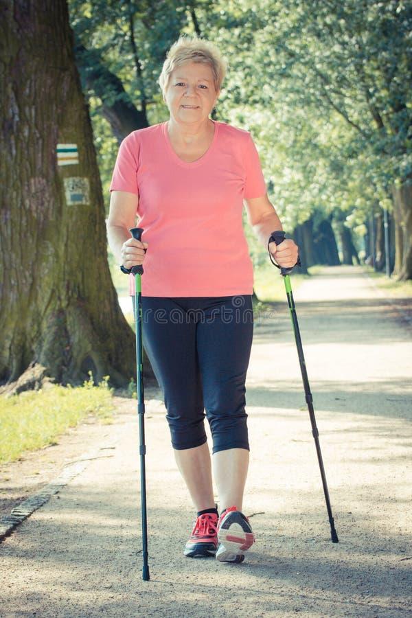 Uitstekende foto, Bejaarde hogere vrouw die het noordse lopen, sportieve levensstijlen in oude dag uitoefenen royalty-vrije stock afbeelding