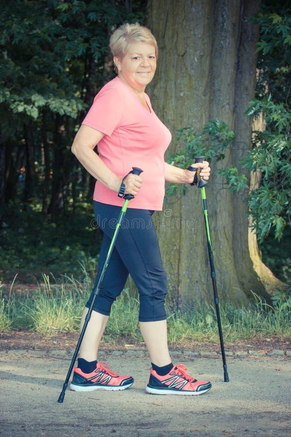 Uitstekende foto, Bejaarde hogere vrouw die het noordse lopen, sportieve levensstijlen in oude dag uitoefenen stock foto