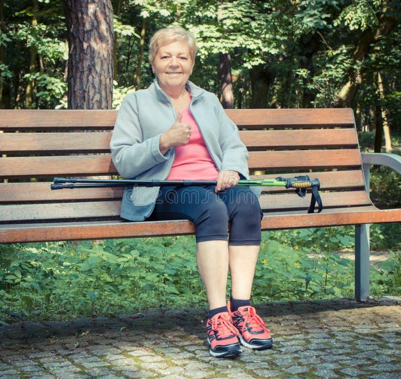 Uitstekende foto, Hogere vrouw die na noordse lopende en tonende duimen omhoog rusten, sportieve levensstijlen royalty-vrije stock foto's