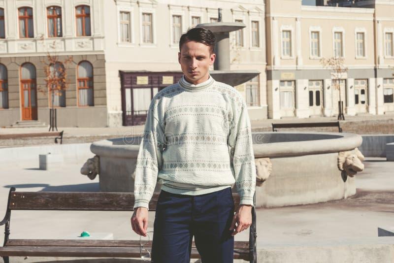 Uitstekende foto van de mens met glazen in witte sweater die zich in F bevinden royalty-vrije stock afbeeldingen