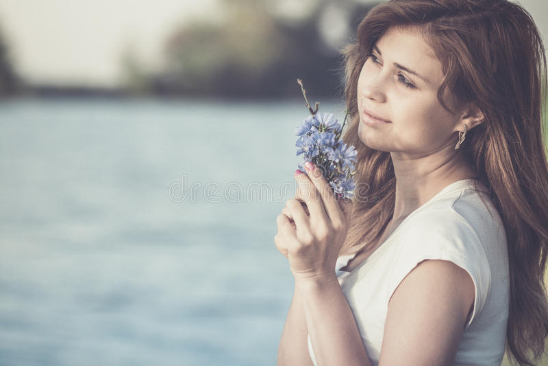 Uitstekende foto van een mooie vrouw met een gevoelig boeket van blauwe wildflowers ter beschikking op aard stock afbeeldingen