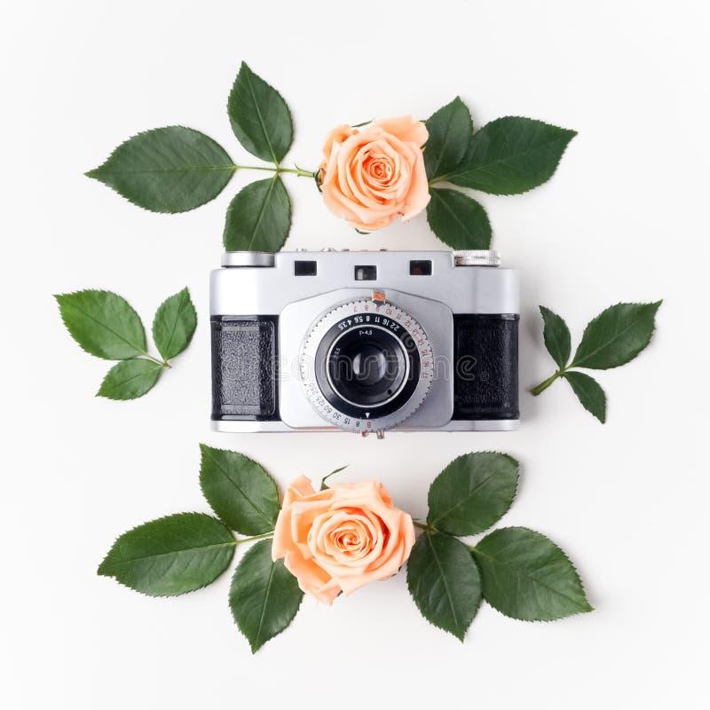 Uitstekende fotocamera, oranje rozen en groene bladeren, hoogste mening Vlak leg stock afbeelding