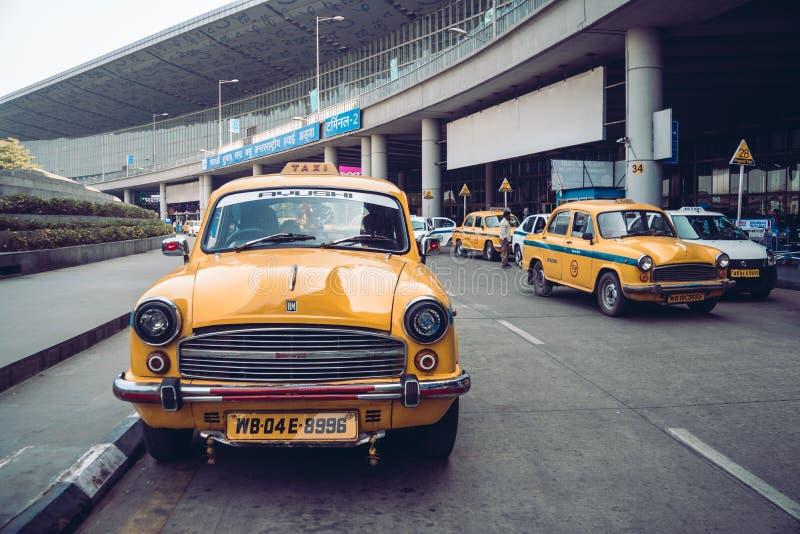 Uitstekende gele taxi in het luchthavenparkeerterrein KOLKATA, INDIA - 26 Januari 2018 stock fotografie